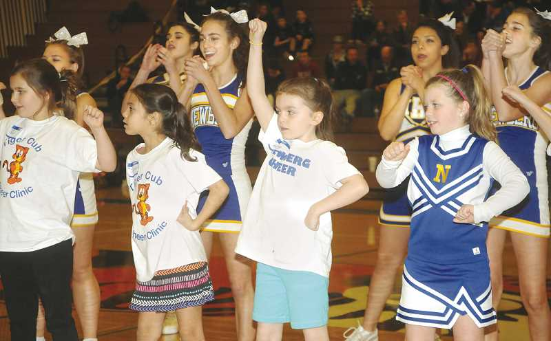 by: SUBMITTED PHOTO - Spirit -- Members of the Newberg High School cheerleading team perform with local youth during halftime of the boys basketball game versus Reynolds pm Dec. 13. The performance was the culmination of the program's annual Tiger Cheer Clinic.