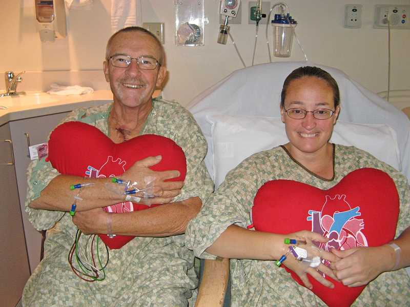 by: SUBMITTED PHOTO COURTESY OF ANGIE SAZ - Angie Sax and her father John Broer, hug 'heart' pillows given to them after open-heart surgery in early October. The pair had similar surgeries only one day apart. Of the photo, Broer noted, 'We were feeling pretty good,' and said he thinks the fact they were together aided in a speedy recovery.