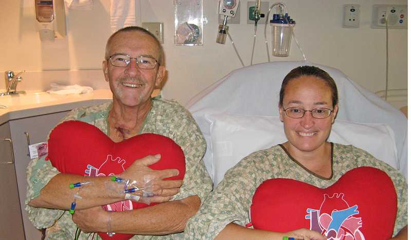 by: SUBMITTED PHOTO COURTESY OF ANGIE SAX - Angie Sax and her father John Broer, hug 'heart' pillows given to them after open-heart surgery in early October. The pair had similar surgeries only one day apart. Of the photo, Broer noted, 'We were feeling pretty good,' and said he thinks the fact they were together aided in a speedy recovery.