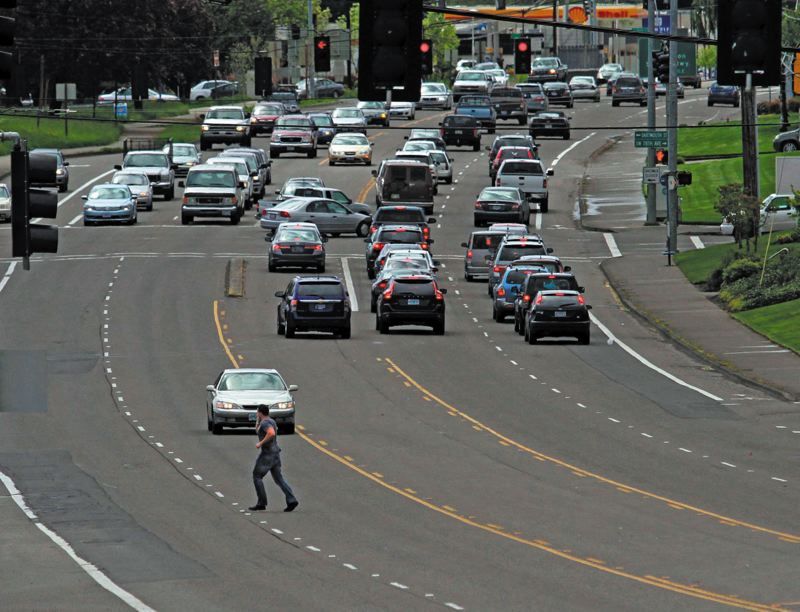by: TRIBUNE FILE PHOTO: JONATHAN HOUSE - A pedestrian makes a dash across a busy Highway 99 in Tigard, near where regional officials are considering a high-capacity transit project. Tigard residents will decide the fate of a ballot measure restricting the project in the city.
