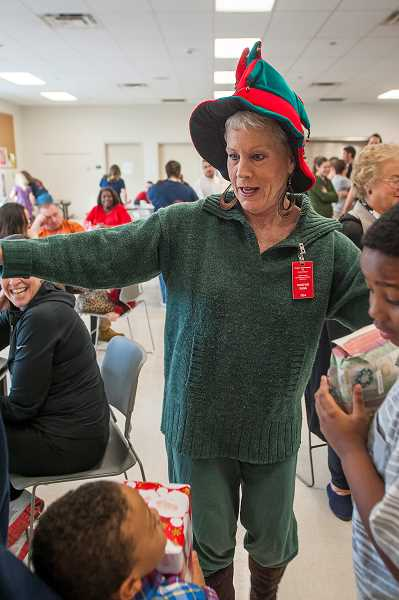 by: JOSH KULLA - Wilsonville resident Susie Sivyer directs the handing out of gifts donated by local residents and businesses Dec. 16 at the 2013 winter Through a Child's Eyes event.