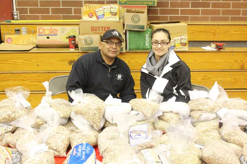 by: MAYGAN BECKERS - First time volunteer Rick Saucedo and five-year volunteer Yasmine Robles get ready to help serve bags of almonds, beans and rice, as families go through stations to pick up items.