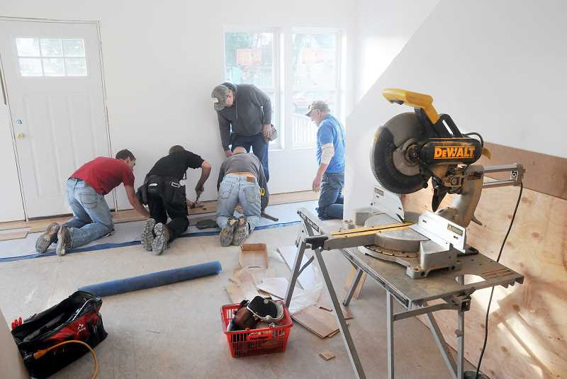 by: GARY ALLEN - Volunteers working at 1309 E. Ninth St. install the hardwood floors in the entryway. This home   is expected to be  completed in February or March.