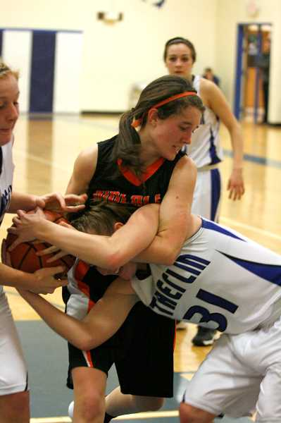 by: PHIL HAWKINS - Amanda Rieskamp fighting for the ball against Sutherlin.