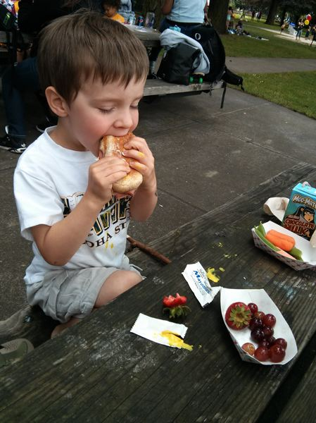 by: SUBMITTED PHOTO - A boy snacks on a sandwich and fruit at a summer food program, made available by Partners for a Hunger-Free Oregon.