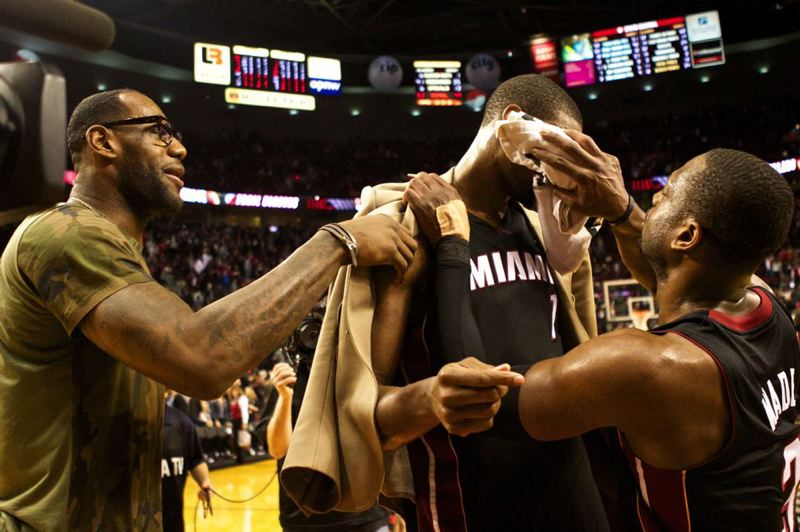 by: TRIBUNE PHOTO: JAIME VALDEZ - Miami Heat teammates LeBron James (left) and Dwyane Wade (right) wipe the sweat off Chris Bosh after he sank the winning 3-pointer Saturday night at Moda Center.