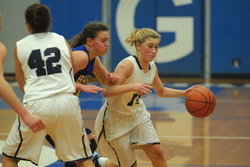 by: PAMPLIN MEDIA GROUP: DAVID BALL - Wilsonville point guard Jocelyn Welberg dribbles out of a crowd during the fifth-place game against Barlow at the Gresham tournament Dec. 28.