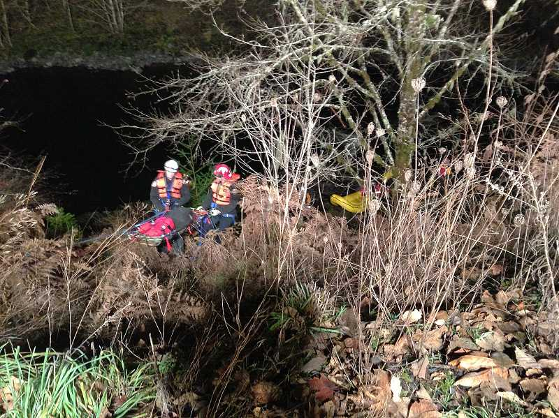 by: CLACKAMAS COUNTY SHERRIFFS OFFICE - Rescue team pulls one of the injured up a cliff after a car crashed upsdie down into the Molalla River early Sunday morning.