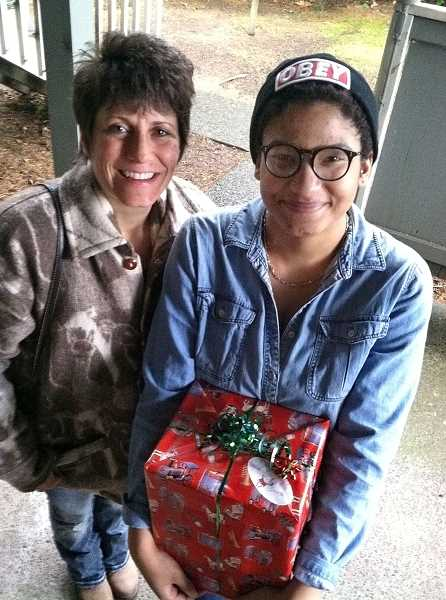 by: ANDY MCCANDLESS - Lake Oswego Police Officer Dawn Pecoraro, left, helped make it a happy Christmas for Danielle and her family in Lake Oswego. Michelle's Love really struck a chord with the police officer.