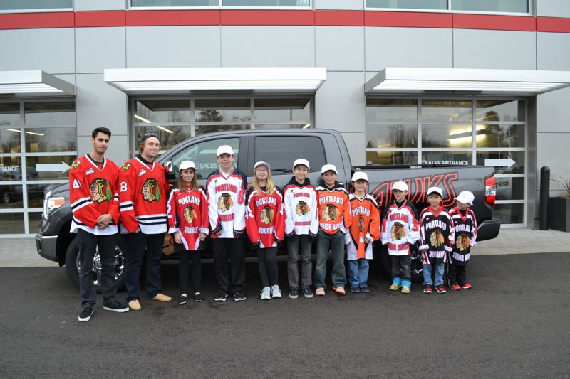 by: COURTESY PHOTO - Portland Winterhawks players Steven Alldridge and Garrett Haar stand in front of the team's new Community Cruiser, a new 2014 Tundra courtesy of Toyota, along with several Junior Hawks players at Beaverton Toyota.