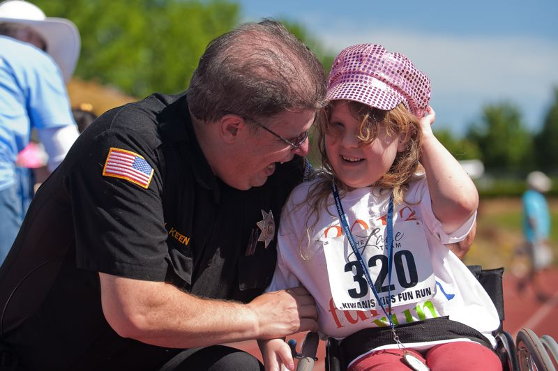 by: SPOKESMAN PHOTO: JOSH KULLA - Wilsonville Police Department School Resource Officer Jim Keen and his daughter, Elisabeth, take part in an Wilsonville institution, the Kiwanis Kids Fun Run.