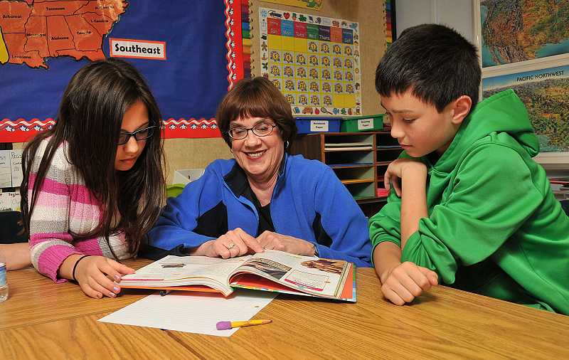 by: REVIEW PHOTO: VERN UYETAKE - Marjorie Reay, the most-senior teacher until she retired, helps Eliza Buchanan and Ben Burk with their school work in 2013.