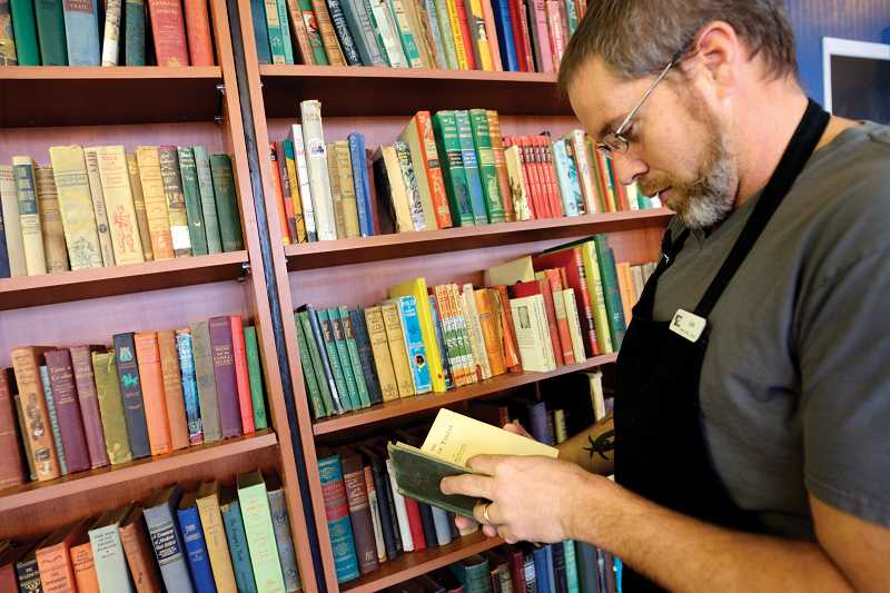 by: KEVIN SPERL - Book and Bean owner, Joe Becker, looks through his collection of classics that attracted Christmas shoppers to his store.