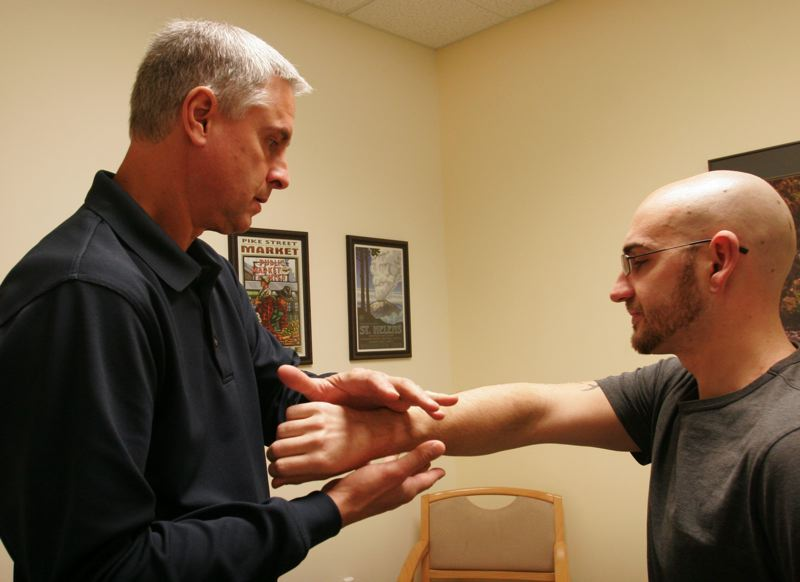 by: OUTLOOK PHOTO: JIM CLARK - George Eischen, director of Sports Care, examines Nathan Tyler who was injured in a bicycle accident.