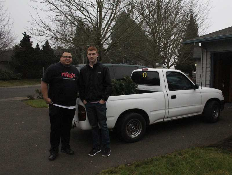 by: MAYGAN BECKERS - Ben Puente, youth pastor at Woodburn Foursquare Church, and Daniel Labunsky, Woodburn High School junior, make one of their first Christmas tree pickup stops to raise money for attending Generation Unleashed.
