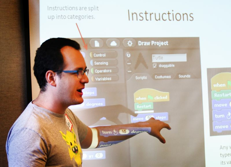 by: OUTLOOK PHOTO: JIM CLARK - Yori Kvitchko, a lead mentor, instructs students in SNAP, describing how they can give a 'turtle' commands to move certain directions.