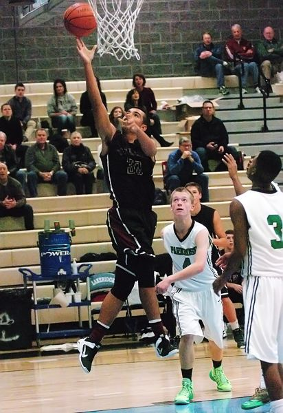 by: DAN BROOD - TO THE RIM -- Tualatin High School sophomore Danté Reid (30) drives past Parkrose junior Caleb Vandermeer and goes up to the basket to score two of his team-high 22 points in Friday's game.