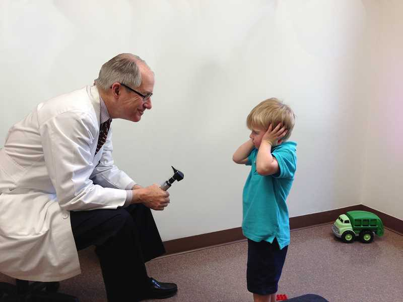 by: SUBMITTED PHOTO - Dr. Donald Palmer interacts with Anthony Miadich during a recent visit to Palmers office at Olsen Medical Clinic in Lake Oswego.