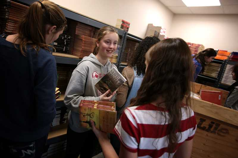 by: TIMES PHOTO: JONATHAN HOUSE - Westside Christian High School student Rachel Nordlund, center, and others unpack boxes of textbooks in a storage room at the schools new home off Pacific Highway. Classes at the school began today.