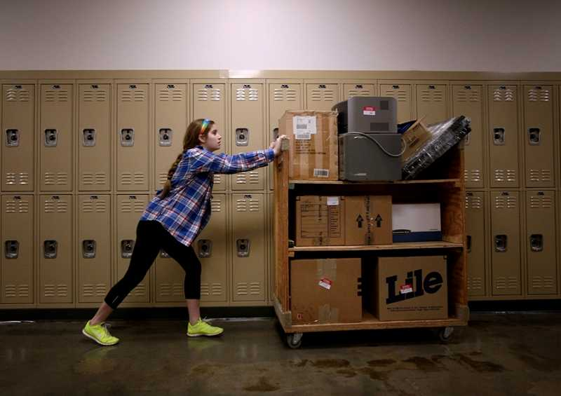 by: TIMES PHOTO: JONATHAN HOUSE - Westside Christian High School student Mikke Rivet helps move boxes and supplies during Mondays move-in day at the new school. For years the school was located in Lake Oswego, but moved into its new home off Pacific Highway and Highway 217 this week.