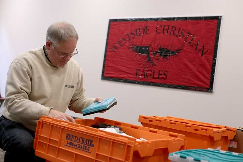 by: TIMES PHOTO: JONATHAN HOUSE - Teacher Don Westerberg unpacks books in his classroom on Monday. A longtime staple of the school, Westerberg has served in one function or another for the past 28 years, from the schools early days with less than 70 students to its current home, which has room for 400.