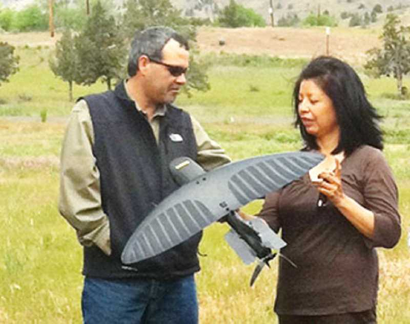 by: SUBMITTED PHOTO - Jim Manion, general manager for Warm Springs Power and Water Enterprises, and Sandra Danzuka, of Warm Springs Ventures, examine a small, hand-launched unmanned aerial vehicle, the Maverick, made by Prioria, which could be among the UAVs testing on the reservation.