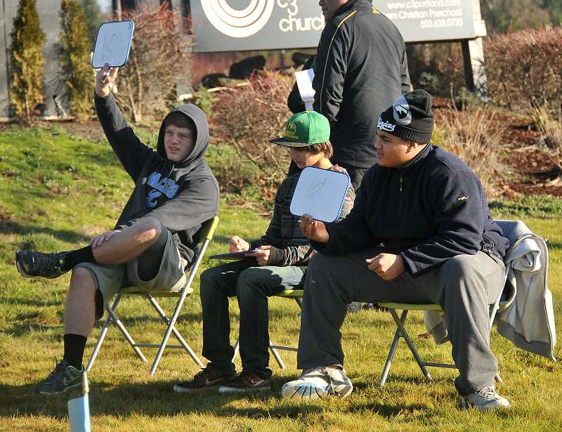 by: REVIEW PHOTO: VERN UYETAKE - Lakeridge rugby team members, from left, Jake Moser, Jacob Gordon and Massen Newton judge contestants.