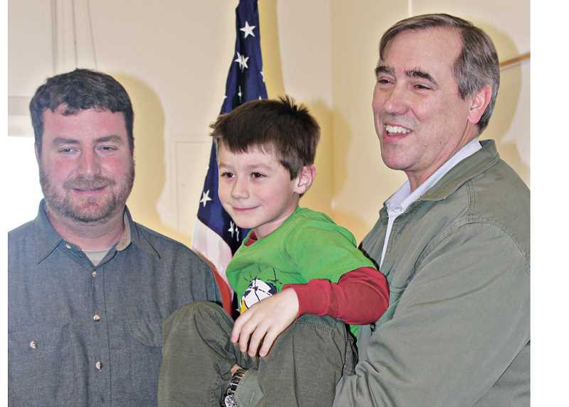 by: HOLLY M. GILL - Sen. Jeff Merkley, right, poses for a photo with 6-year-old Jacob Turo, and Scott Turo, left.
