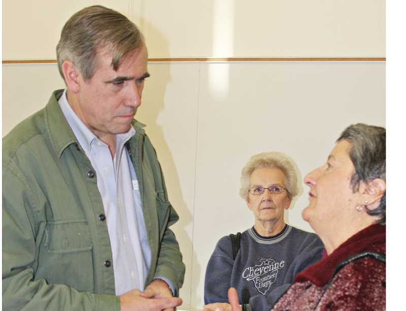 by: HOLLY M. GILL - Sen. Jeff Merkley listens to Carol Leone, right, while Louise Muir, center, awaits her turn at the Jan. 4 town hall at the COCC Madras campus.
