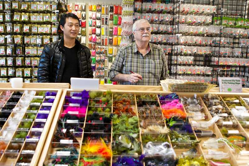 by: TIMES PHOTO: JAIME VALDEZ - Haibin Wang, owner Fish-Field Inc., and store employee Tim Ganley have opened a fishing store in Tigard that will appeal to anglers.