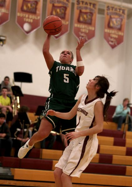 by: JONATHAN HOUSE - JUMPER -- Tigard High School senior guard Lexi Carter (left) shoots over Milwaukie's Karissa Delauna in Tuesday's game.