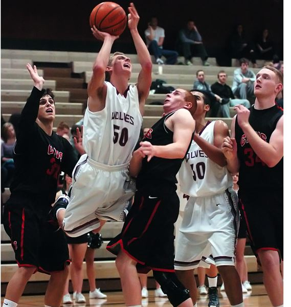 by: DAN BROOD - FINDING A SEAM -- Tualatin High School senior guard Joey Fishback (50) goes up between Clackamas' Andrew Gutwig (left) and Cade Wilkins in Friday's game.