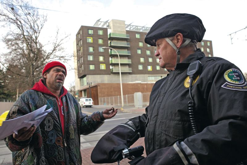 by: TRIBUNE PHOTO: JAIME VALDEZ - Retired Portland police officer Jim Bare talks to Eric Turner with Bud Clark Commons in the background. Bare patrols the area around The Apartments at Bud Clark Commons as part of a contract with Portland Patrol Inc.