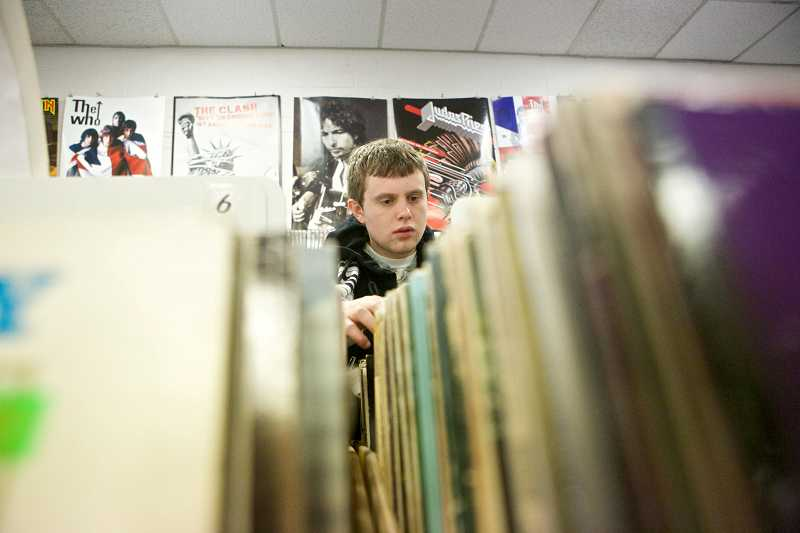 by: TIMES PHOTO: JAIME VALDEZ - South Beaverton resident Alec Cartwright rifles through records at Everyday Music in Cedar Hills. A student at Portland Community College's Sylvania Campus, Cartwright is a loyal customer at the vinyl, CD and DVD store.