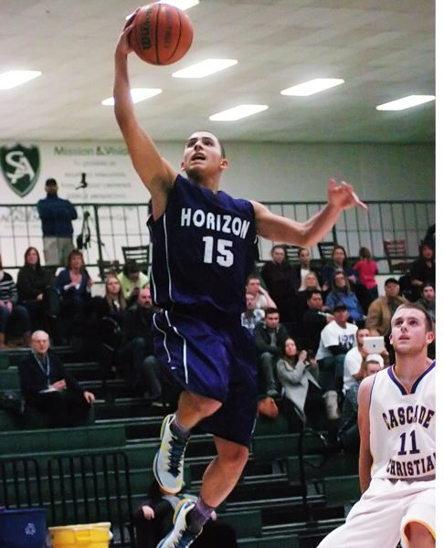 by: DAN BROOD - GOING UP -- Horizon Christian junior Noah Jones goes up to the basket in front of Cascade Christian's Kenny Laws during the title game of the Crusaders New Year's Invitational, held Saturday at Salem Academy.