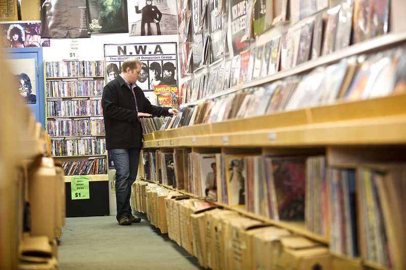 by: TIMES PHOTO: JAIME VALDEZ - Scott Canfora of Tualatin flips through record albums in a aisle dedicated to vinyl at Everyday Music in Beaverton.