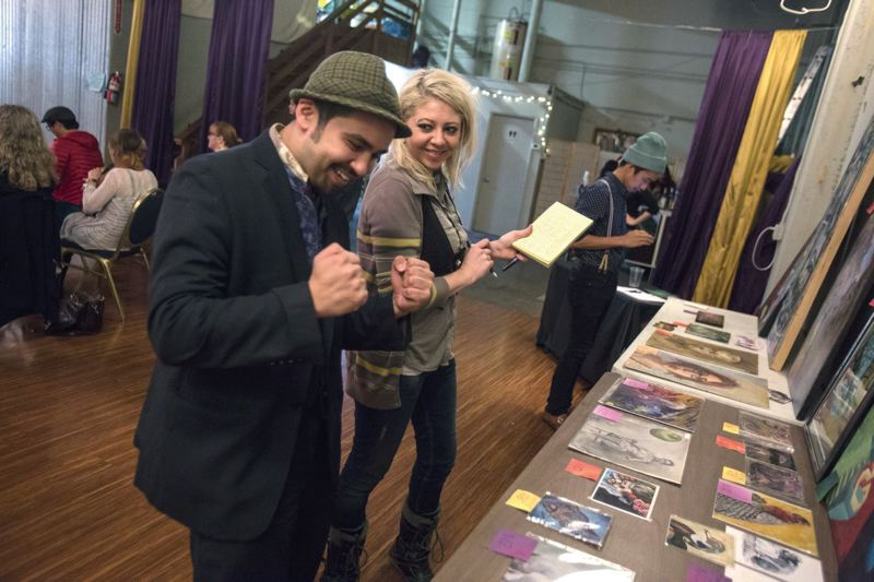by: TRIBUNE PHOTO: JONATHAN HOUSE - Portland 4 the Philippines organizers Djo Fortunato and Riannah Weaver check out their art auction during last Saturdays fundraiser.