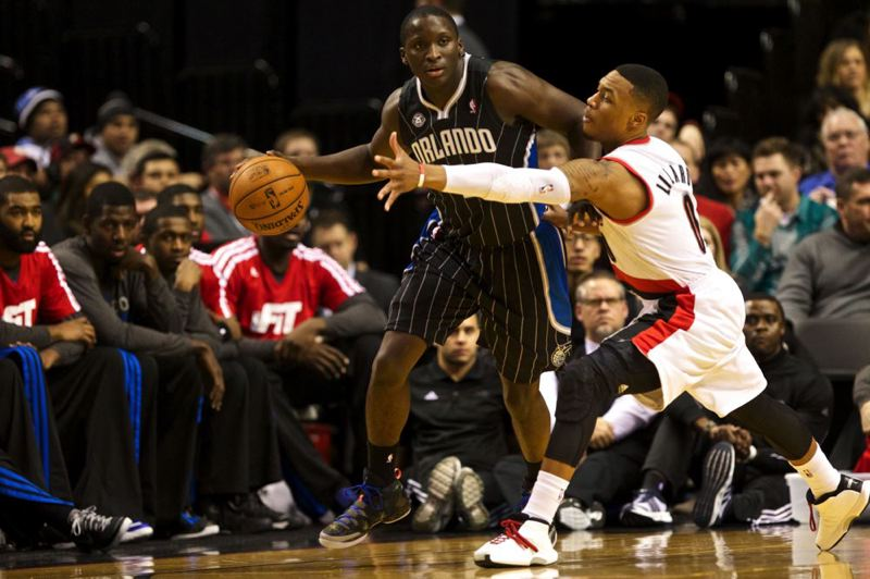 Orlando's Victor Oladipo keeps the ball from Damian Lillard in the first half.