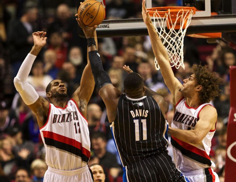LaMarcus Aldridge (left) and Robin Lopez (right) converge on Glen Davis at the basket.