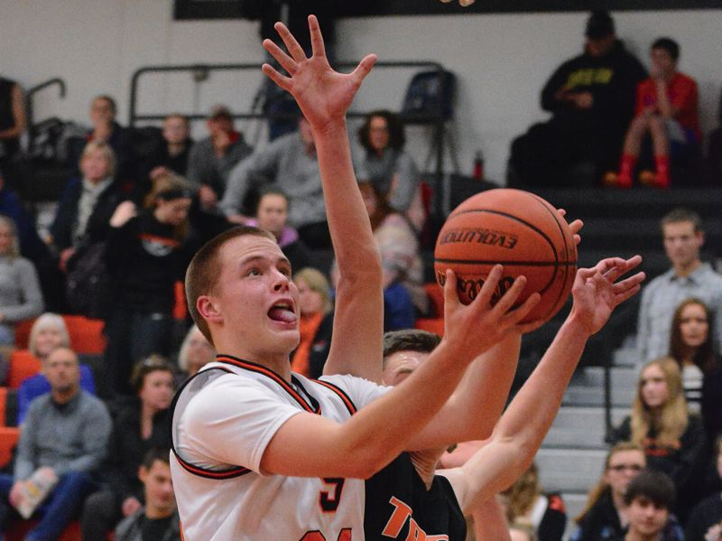 by: JOHN WILLIAM HOWARD - Senior Mitch Davis fights for two of his team-high 16 points during the Indians' win over Taft. Scappoose has now won two in a row, and will go for three on Friday evening in Central.