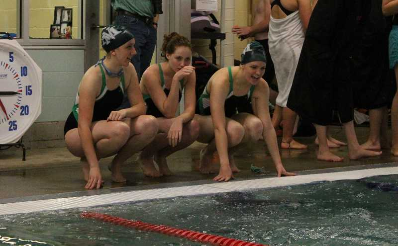 by: CORY MIMMS / PAMPLIN MEDIA GROUP - Members of the North Marion girls swimming team follow the action Jan. 8 at Molalla High School. The Huskies took second place in boys and girls competition.