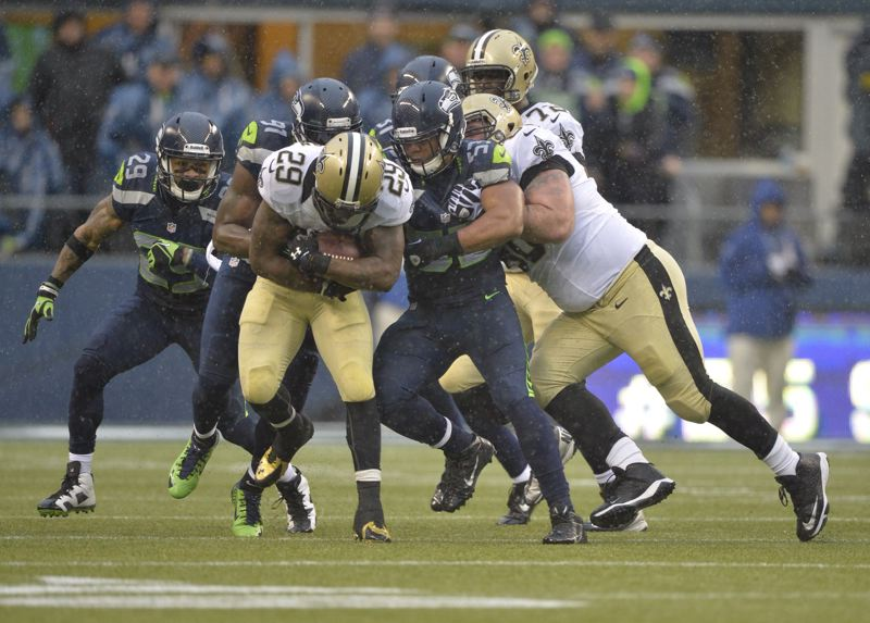 The Seahawks gang-tackle New Orleans running back Khiry Robinson.