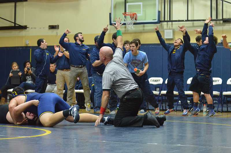 by: JEFF GOODMAN / PAMPLIN MEDIA GROUP - The Canby wrestling team reacts to senior Alejandro Sandoval's pin in the heavyweight bout Jan. 9 in its league-opening home dual against Oregon City.