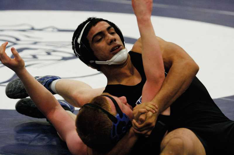 by: PHIL HAWKINS - Woodburn's Rodolfo Hernandez scores a first-period pin over Gervais Byron Thiessen at Woodburn High School on Saturday. Hernandez pinned all four of his opponents on the day and was one of four Bulldog wrestlers to go undefeated on the day.