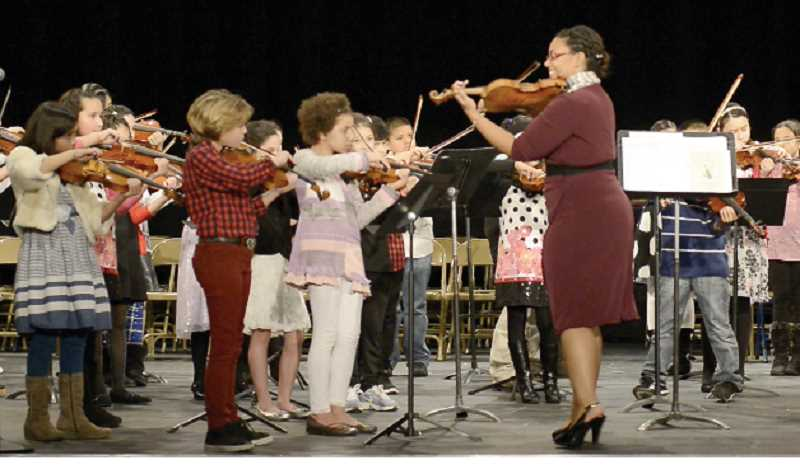 by: SUBMITTED - Violin instructor Kelsey Aronstein leads her students in a concert performance. Aronstein offers lessons twice a week to students in Woodburn's After School Club program.