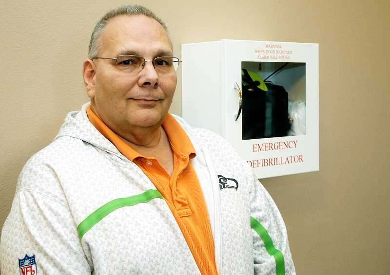 by: SETH GORDON - Lifesaver -- Former reserve sergeant Ron Enkelis stands next to the automated external defibrillator (AED) device that helped save his life after he went into cardiac arrest Dec. 1 at Grace Baptist Church.