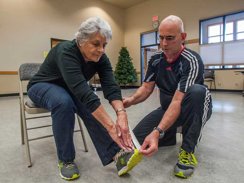 by: JOSH KULLA - Wilsonville resident Delores Mouck, left, has her flexibility measured by Wilsonville Community Center trainer Brad Moore as part of the centers new fitness testing program for seniors.