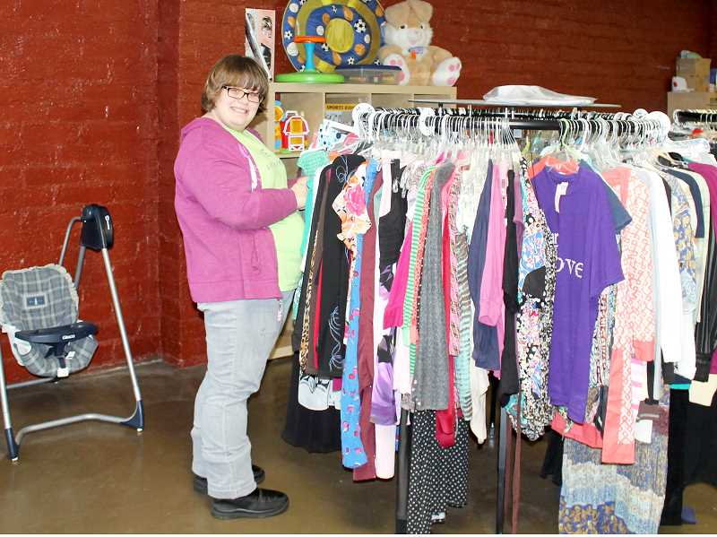 by: CORY MIMMS - Christa Daniels sorts clothing at Little Sweet Peas' new location.