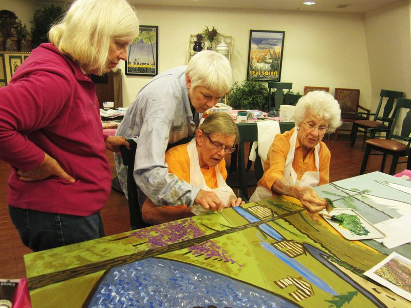 by: SUBMITTED PHOTO - Lake Oswego art therapist Sharon Evers (middle back) helps a Springridge Court resident work on a large mural that recently was hung in the dining room at the Charbonneau assisted living facility.