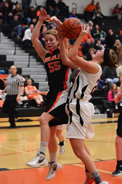 by: JOHN WILLIAM HOWARD - Lacey Updike gets fouled by Molalla's Josie Child during the first half of Tuesday's victory. Updike led the home team in scoring with 16 points.